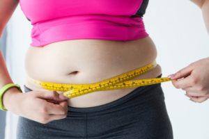 ウエストを測る太った女性の画像